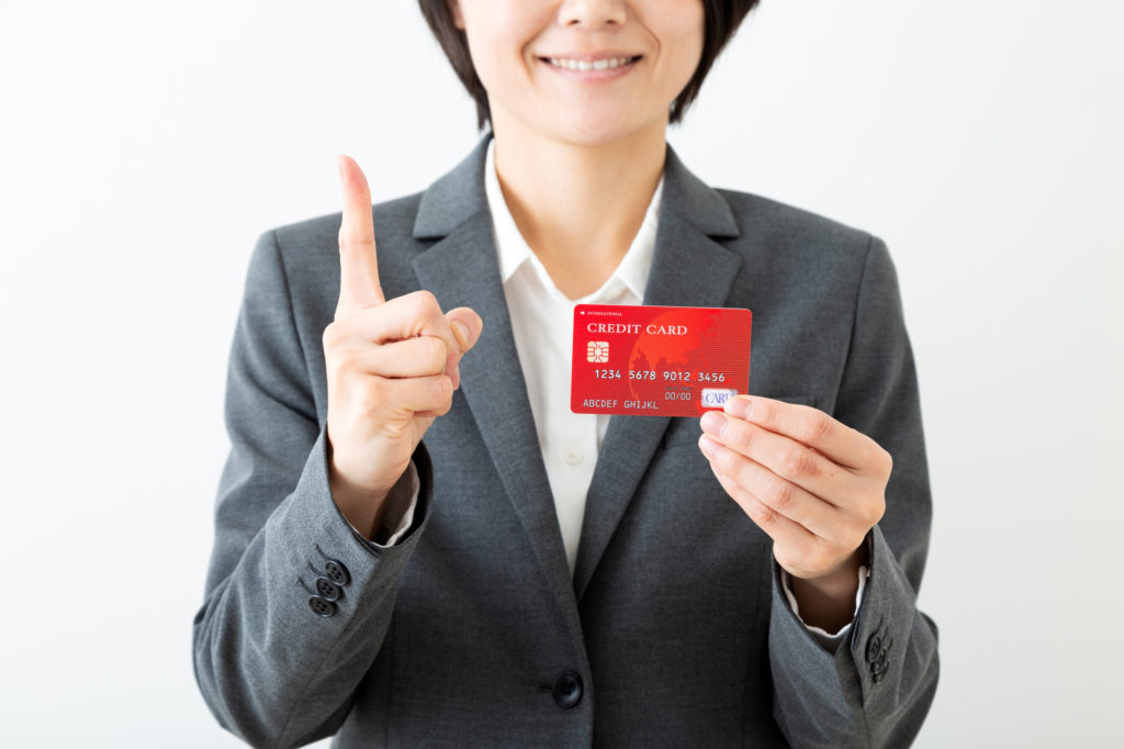 女性 クレジットカード 指差し